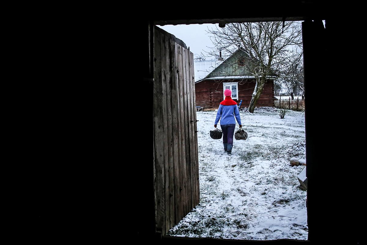 Олеся набирает брикет в лукошки в сарае, который находится рядом с домом. Фото: Евгений  ТИХАНОВИЧ