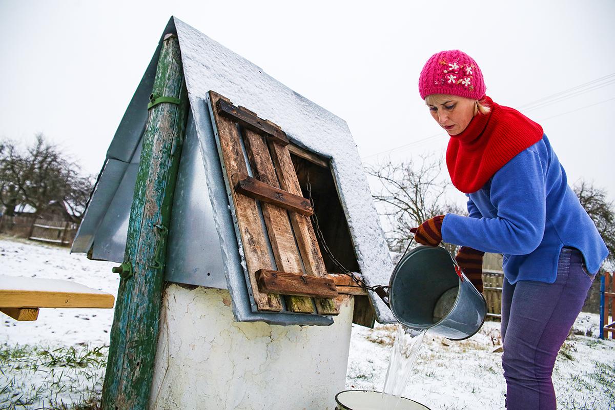 Олеся набирает воду из колодца для Зои Ивановны на несколько дней вперед. Фото: Евгений ТИХАНОВИЧ