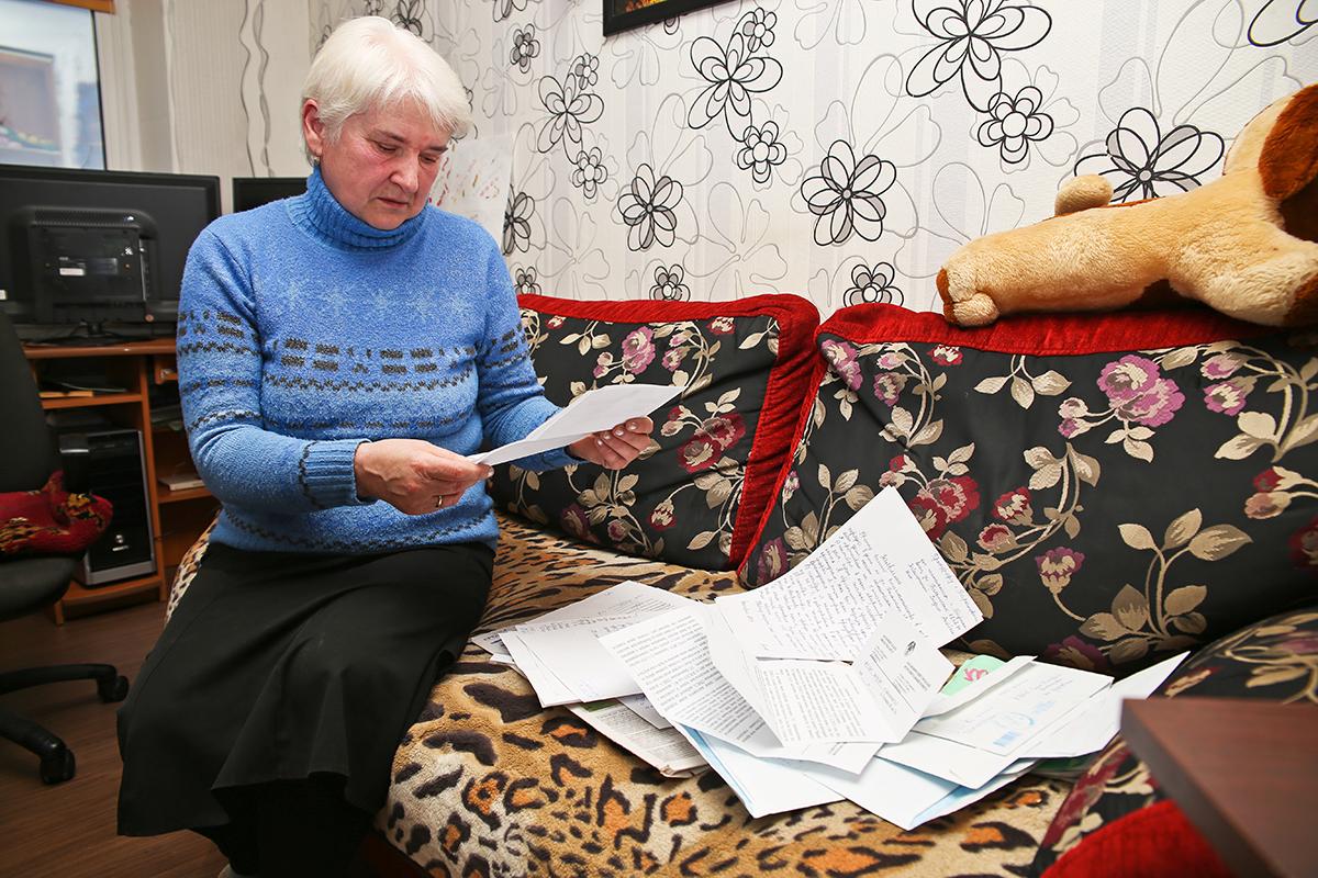 Лидия Заболотная читает очередное письмо, в котором коммунальщики обещают решить проблему с дырявой крышей. Фото: Евгений ТИХАНОВИЧ