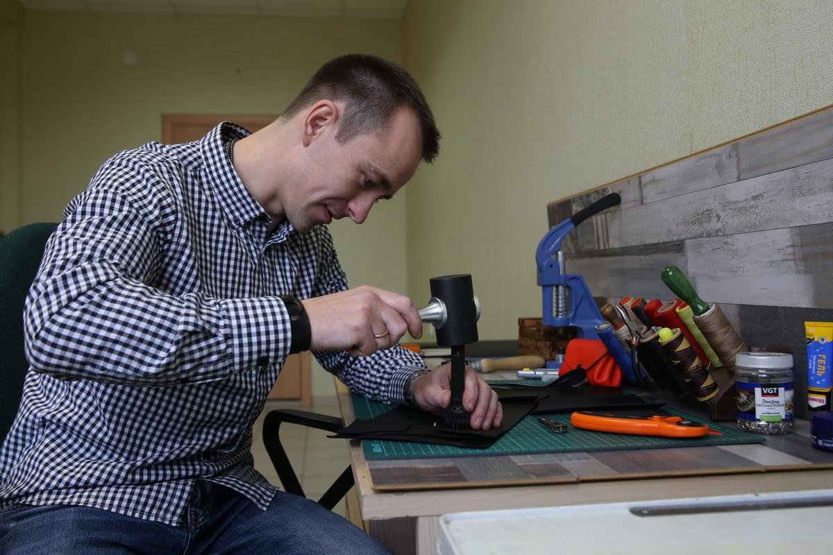 Павел Шкуда пробивает отверстия под шов в будущем кошельке. Фото: Евгений ТИХАНОВИЧ