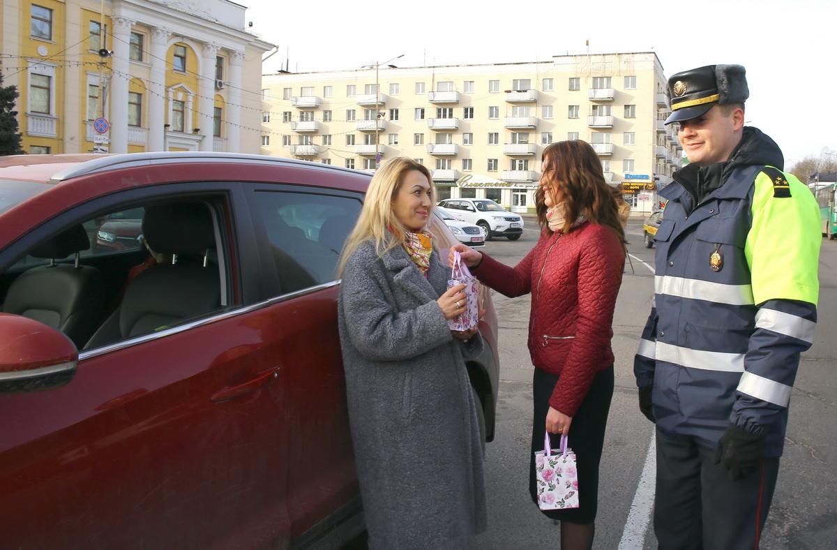 Старший лейтенант милиции Дмитрий Сологуб и Надежда Вилента поздравляют автоледи с 8 Марта. Фото: Татьяна МАЛЕЖ