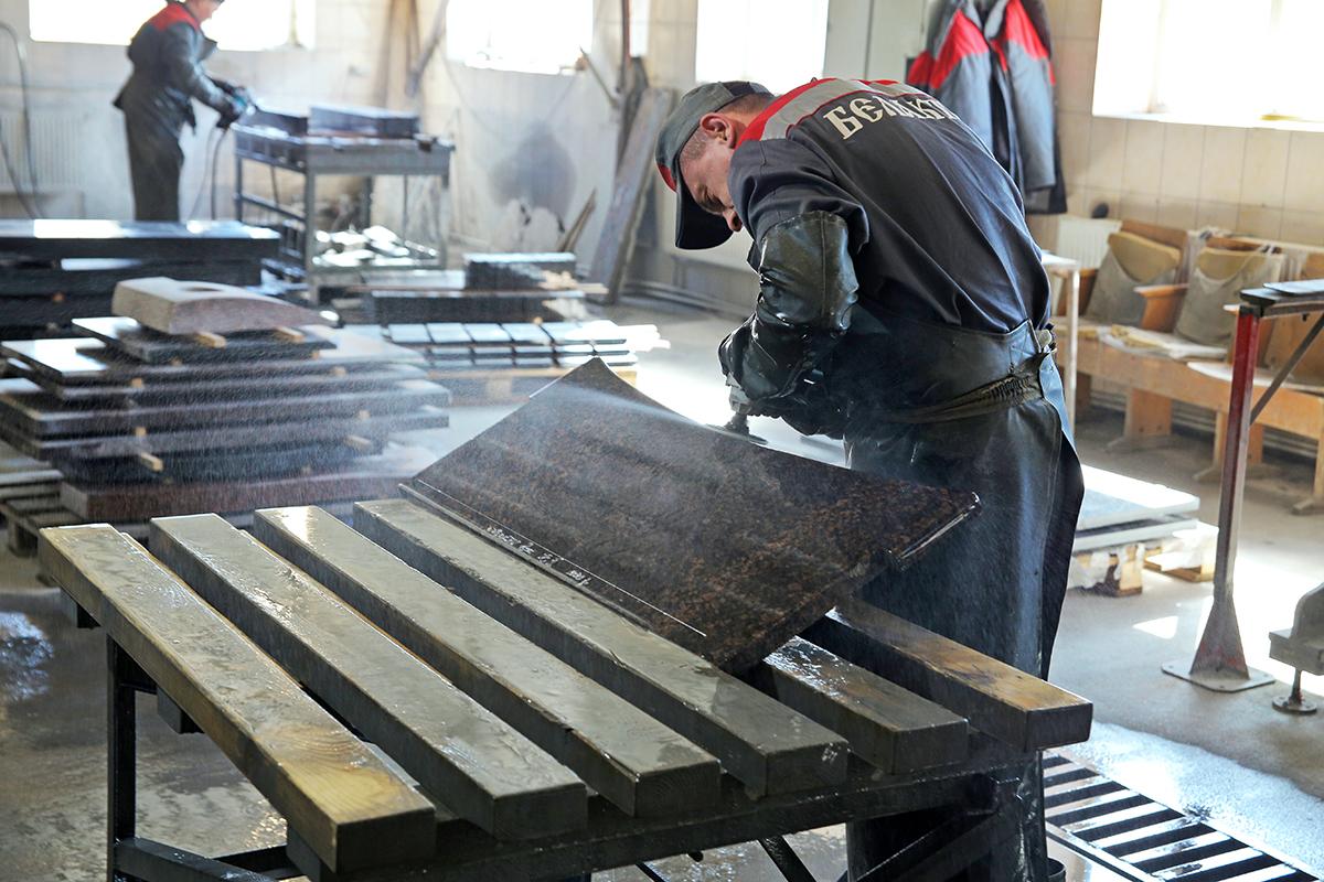 Александр Филончик, распиловщик камня, шлифует гранитную плиту. Фото: Евгений ТИХАНОВИЧ