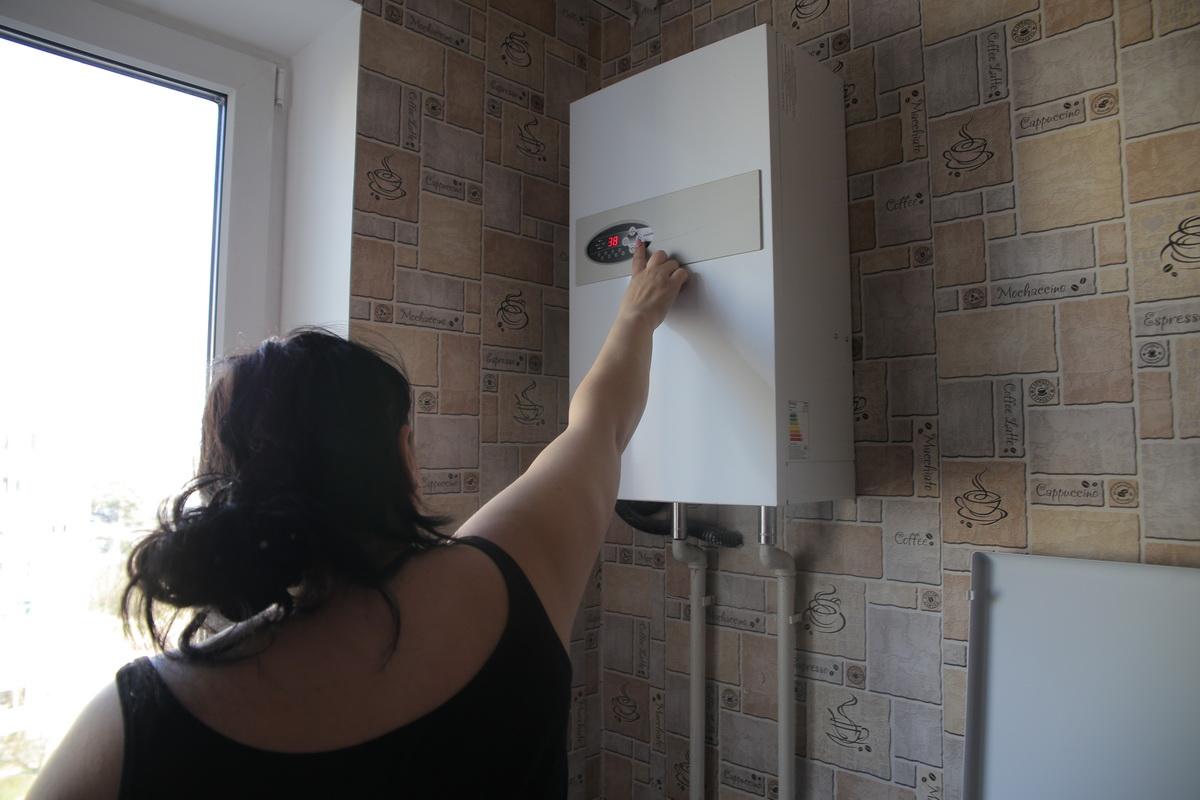 Жительница дома №11 на ул. Орджоникидзе регулирует температуру на электрокотле.  Фото: Евгений ТИХАНОВИЧ