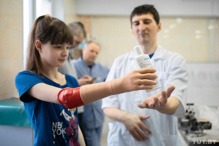 Биопротез в действии: Ульяна пробует держать предметы. Фото: Дмитрий Брушко / TUT.BY