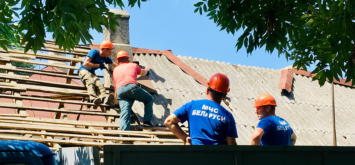 Сотрудники МЧС разбирают крышу аварийного дома. Фото: Евгений ТИХАНОВИЧ