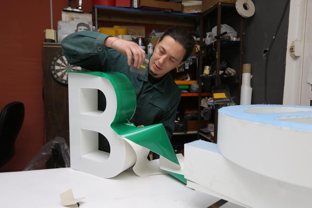 Максим Сафонов оклеивает объемную букву для новой рекламной вывески.  Фото: Александр ЧЕРНЫЙ