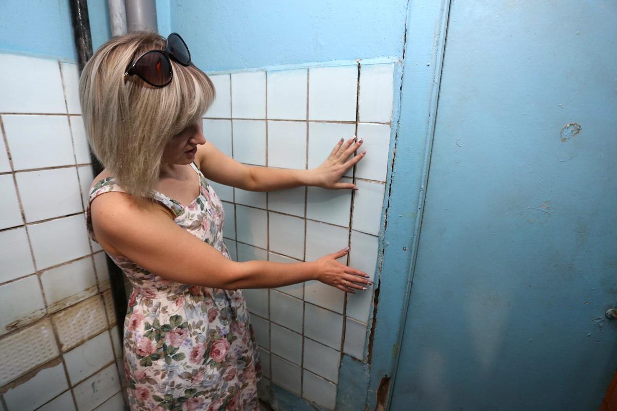 Жительница общежития на улице Промышленная, 11А Вера Максимович показывает трещины на стенах в санузле. Фото: Александр ЧЕРНЫЙ