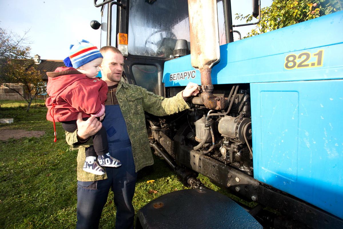 Муж Елены Дегиль Алексей с младшим сыном Иваном возле собственного трактора. Фото: Александр ЧЕРНЫЙ
