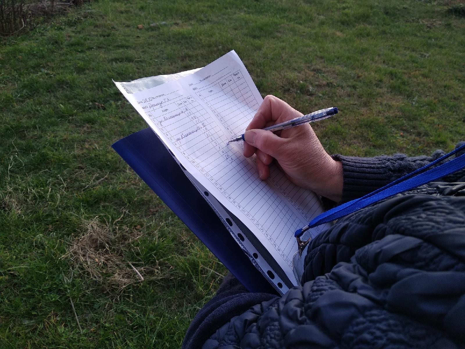 Переписчик ставит точку напротив адреса с уведомлением. Фото: Ирина Комик