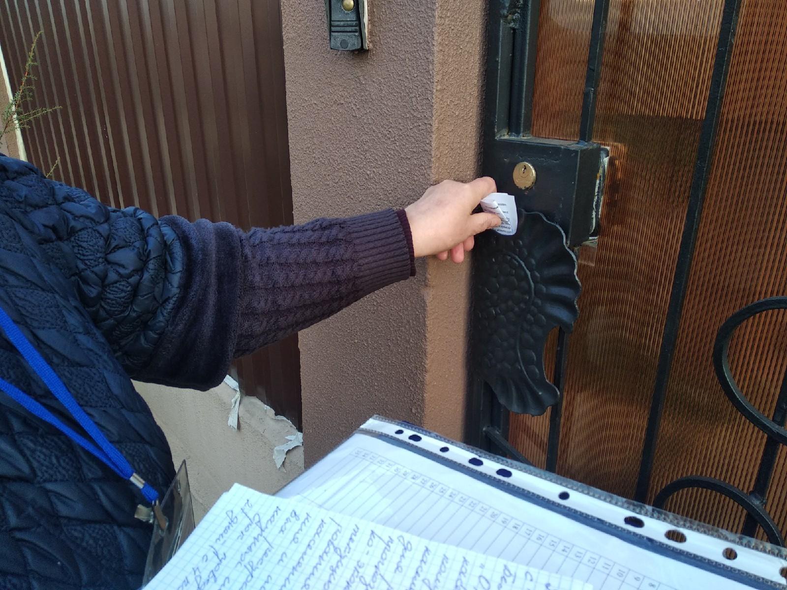 Тамара Анатольевна оставляет уведомление в  калитке. Фото: Ирина Комик