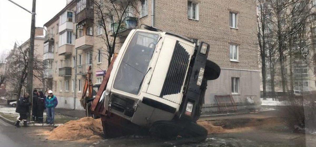 Грузовик дорожных рабочих почти полностью провалился в яму в Минске. Фото