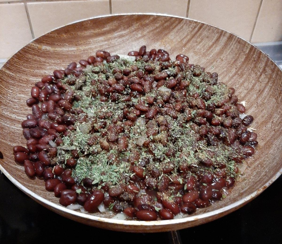 Когда лук стал полупрозрачным, выкладываем на сковороду фасоль, солим, добавляем хмели-сунели и кинзу или петрушку. Фото: Анна РОМАНОВА-КОЛОСОВСКАЯ