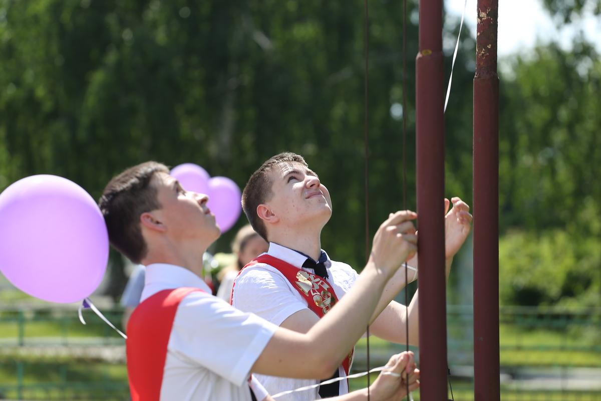 Выпускники подняли флаг Беларуси на торжественной церемонии вручения аттестатов. Фото: Андрей БОЛКО