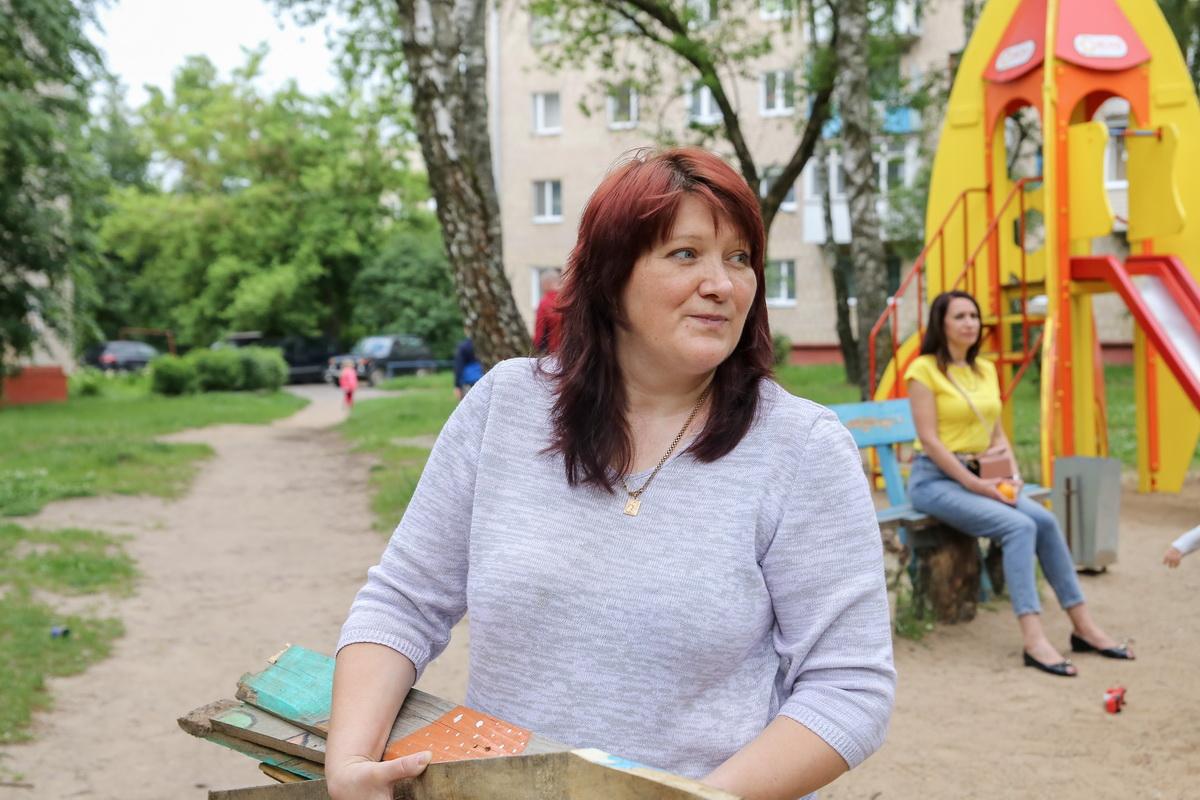 Ирина Юреня, мама-инициатор строительства детской площадки, убирает обломки домика. Фото: Андрей БОЛКО