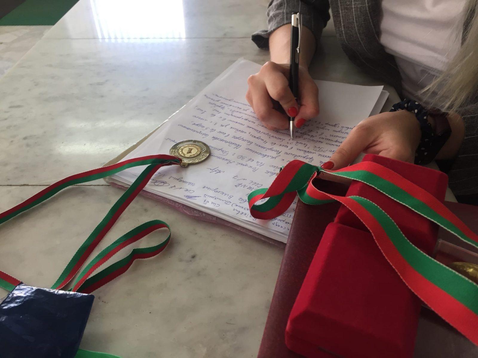 Александра Рогоцкая, одна из барановичских выпускников, указывает в обращении весь перечень медалей, грамот и других наград. Фото: Диана КОСЯКИНА