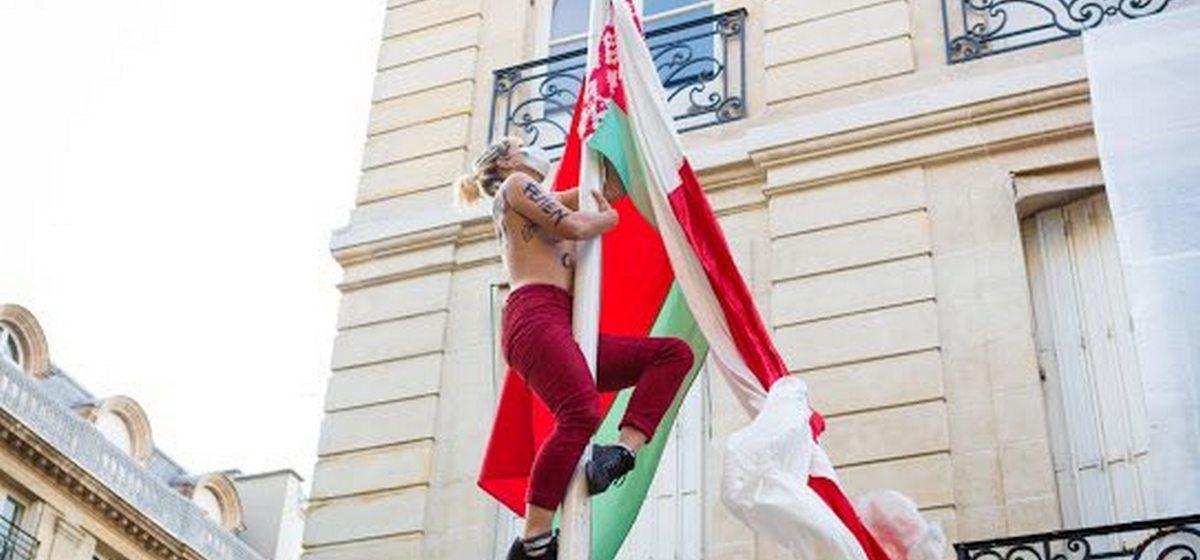 Голая активистка Femen взобралась на флагшток и вывесила бело-красно-белый флаг на территории посольства Беларуси в Париже. Видео