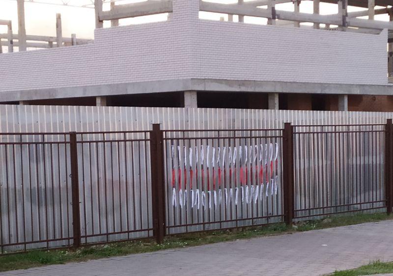 Бело-красно-белый флаг из ленточек на заборе строящейся школы в Боровках. Фото: читатель Intex-press