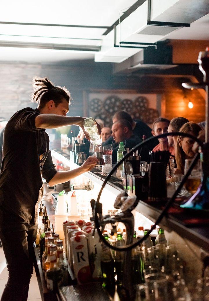Антон Бычков готовит напитки за барной стойкой.
