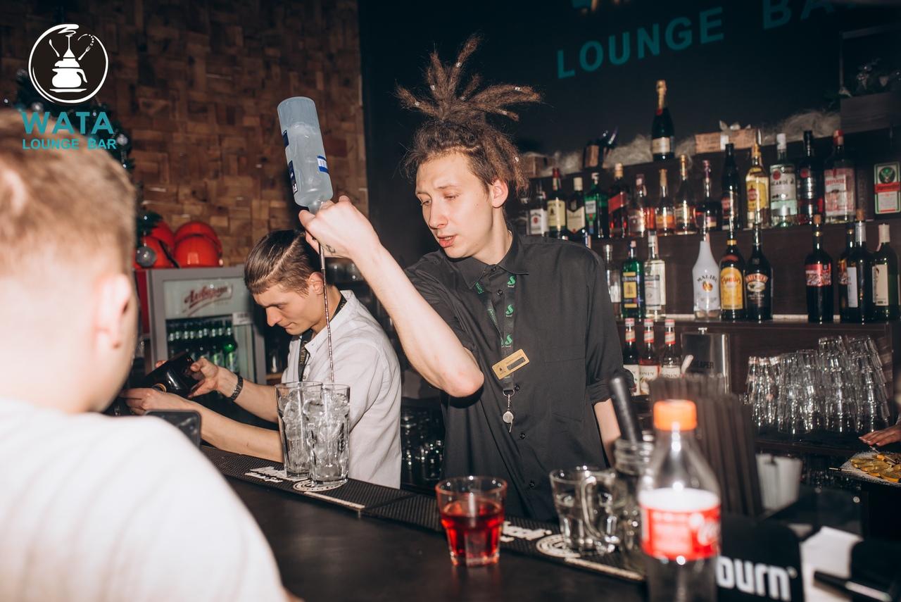 Антон Бычков наливает коктейли за барной стойкой.