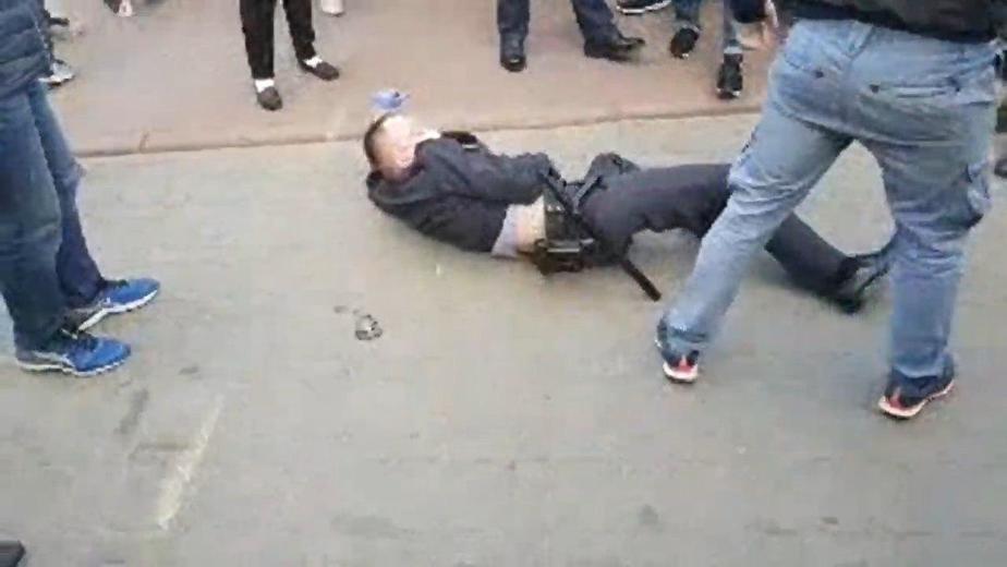 Милиционер лежит на земле во время пикета Тихановской 29 мая 2020 года. Кадр из видео