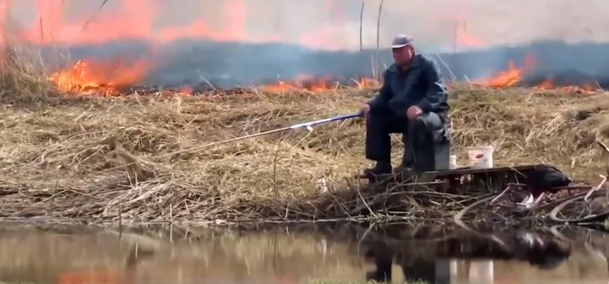 Рыбак продолжал ловить рыбу в Слуцке, несмотря на пылающее поле за спиной. Выглядит очень эпично