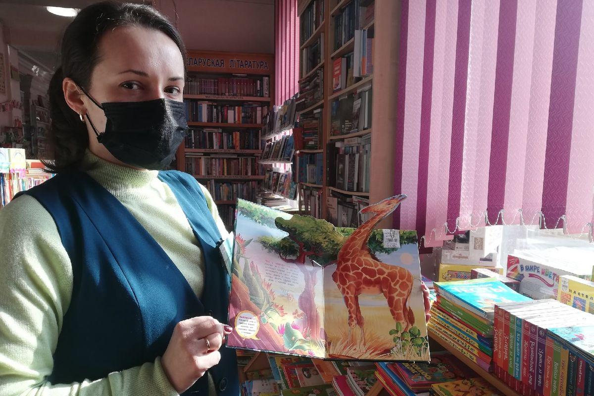 Продавец в книжном магазине на улице Советской показывает одну из книг, которые часто покупают для детей. Фото: Кристина СОБИНСКАЯ