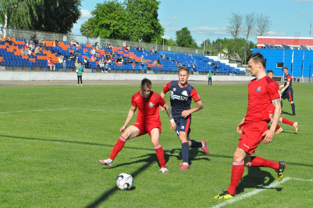 Игрок ФК «Барановичи» Артур Тишко (в красной форме) борется за мяч с футболистом гомельского «Локомотива».